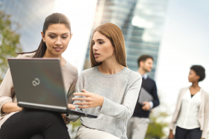Header image of two women working with a laptop outside